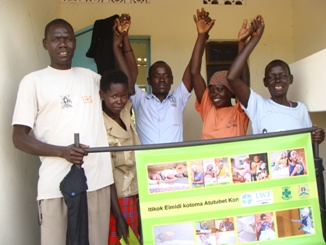 LWF staff Emmanuel Emenyu center with VHTs who have received IEC materials.jpg